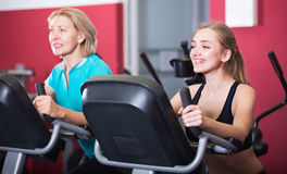 Females riding stationary bicycles in gym Stock Photo