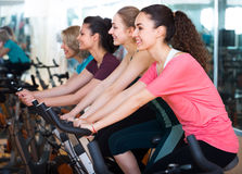 Females riding stationary bicycles Stock Photo