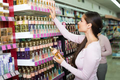 Females selecting fragrance in store Stock Image