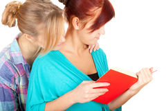 Females teenage friends reading red book Royalty Free Stock Photo