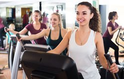Females training on elliptical trainers in fitness club. Positive females training on elliptical trainers in fitness club Stock Image