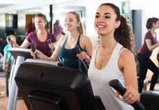 Females training on elliptical trainers in fitness club. Positive american females training on elliptical trainers in fitness club Stock Photo
