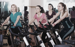 Females training on exercise bikes. Positive females of different age training on a exercise bikes together Stock Photos