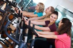 Females training on exercise bikes stock photo
