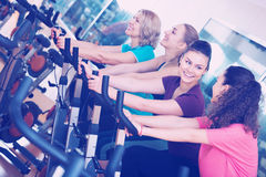 Females training on exercise bikes Stock Images