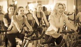 Females training on exercise bikes stock photos