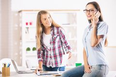 Females working and talking on phone Stock Image