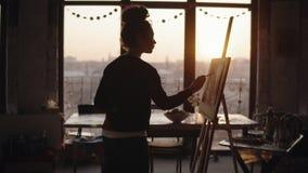 Femaly konstnär som arbetar i en minimalistic vind utformad konststudio, fulländande övre hennes arbete som tillfogar små detaile lager videofilmer
