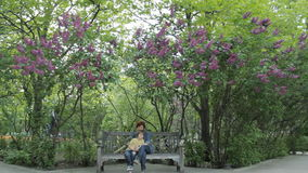 Femaly in the park. Son with mother sitting on the bench in the park in spring stock footage