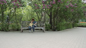 Femaly in the park. Son with mother sitting on the bench in the park in spring stock video