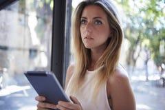 Femelle à l'aide de son comprimé numérique portatif pour le travail à distance pendant le temps de récréation Images stock