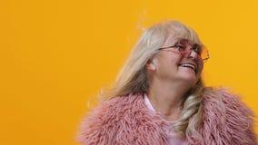 Femelle âgée élégante en lunettes roses et fourrure posant le fond lumineux, modèle clips vidéos