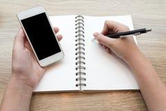 Femelle étudiant et apprenant avec un mobile dans un café photographie stock