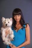 Femelle adulte principale tenant le chien blanc de terrier Photos stock