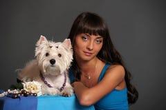 Femelle adulte principale tenant le chien blanc de terrier Photographie stock libre de droits