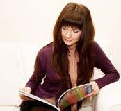 Femelle affichant un magazine au temps de thé Photo libre de droits