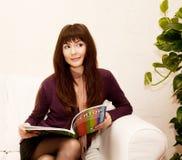 Femelle affichant un magazine au temps de thé Images stock