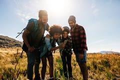 Femelle africaine avec des amis prenant des photos dans la campagne Photographie stock