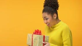 Femelle africaine avec plaisir regardant le boîte-cadeau à disposition, recevant le bonheur actuel banque de vidéos