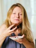 Femelle appréciant un 'brownie' de chocolat Photographie stock libre de droits