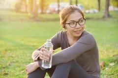 Femelle asiatique eau potable se repose et  Photos libres de droits
