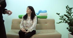 Femelle attendant son rendez-vous sur le sofa, et deux personnes marchent autour clips vidéos
