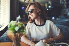 Femelle attrayant heureux attendant ses amis tout en se reposant dans l'intérieur moderne de café Images stock