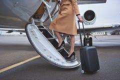 Femelle avec des bagages se déplaçant aux avions Photographie stock libre de droits