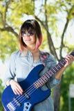 Femelle avec des lunettes de soleil jouant la guitare dehors Image libre de droits