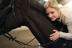 Femelle avec des yeux fermés étreignant le cheval foncé Photographie stock libre de droits
