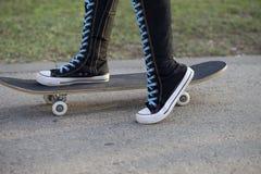 Femelle avec la planche à roulettes dans de hautes espadrilles de genou. Images libres de droits