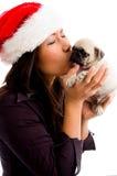 Femelle avec le chapeau de Noël et le chiot de baisers Images stock