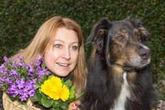 Femelle avec le panier et le chien de fleur Photo stock