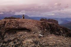 Femelle avec le sac à dos au bord du regard de roche sur les monastères de Meteora Meteora en Grèce dans la Thessalie au mornin t Images libres de droits