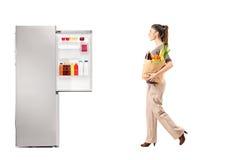 Femelle avec le sac de papier plein des épiceries marchant vers le réfrigérateur Images libres de droits