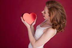 Femelle avec les cheveux rouges tenant la forme de coeur Images libres de droits