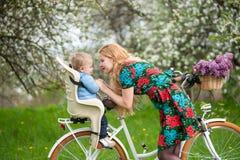 Femelle blonde avec la bicyclette de ville avec le bébé dans la chaise de bicyclette Photos libres de droits
