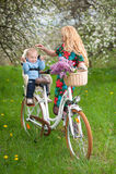 Femelle blonde avec la bicyclette de ville avec le bébé dans la chaise de bicyclette Image stock