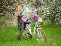 Femelle blonde avec la bicyclette de ville avec le bébé dans la chaise de bicyclette Images stock