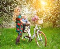 Femelle blonde avec la bicyclette de ville avec le bébé dans la chaise de bicyclette Image libre de droits