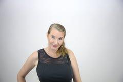 Femelle blonde mûre souriant regardant l'appareil-photo dans le dessus noir Photographie stock libre de droits