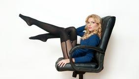 Femelle blonde sexy attirante avec le chemisier bleu lumineux et les bas noirs posant se reposer de sourire sur la chaise de burea Photo stock