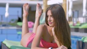 Femelle chic heureuse dans le maillot de bain se reposant sur le salon de cabriolet par le poolside à la station de vacances chèr banque de vidéos