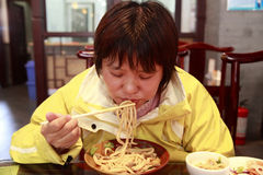 Femelle chinoise mangeant des nouilles Photographie stock