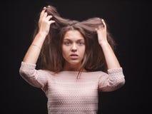 Femelle choquée tirant ses cheveux malades sur un fond noir Femme magnifique peu satisfaite de ses cheveux Concept de routine de  image stock