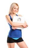 Femelle d'athlète retenant une échelle de poids Image stock