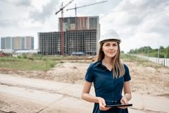 femelle d'ing?nieur de construction Architecte avec une tablette ? un chantier de construction Regard de jeune femme in camera photo stock