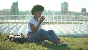 Femelle d'une chevelure bouclée heureuse mangeant la pomme fraîche et s'asseyant sur la pelouse verte, santé banque de vidéos