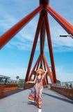 Femelle dans la longue robe des modèles vibrants marchant à travers le pont de croisement de Yandhai Nepean images libres de droits