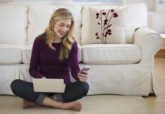 Femelle dans la salle de séjour avec l'ordinateur portatif et le téléphone portable Photos libres de droits
